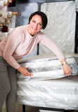 Brunette choosing sleeping mattress Royalty Free Stock Photo
