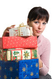 Brunette with Christmas presents. Young brunette with pile of Christmas presents. Isolated over white Stock Photography