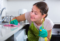 Brunette cleaning in domestic kitchen Stock Photo
