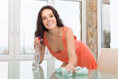 Brunette cleaning glass table stock image