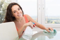Brunette cleaning glass table Royalty Free Stock Images