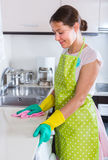 Brunette cleaning in the kitchen Stock Photo