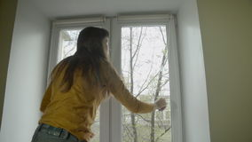 The brunette closes the window, then lowers the roller blind. stock video
