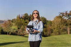 Brunette Coed Flying A Drone. A brunette coed flying a drone in the outdoors stock photo