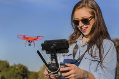 Brunette Coed Flying A Drone. A brunette coed flying a drone in the outdoors royalty free stock photo
