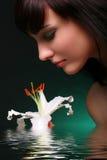 Brunette com as flores do lírio branco na água Fotos de Stock Royalty Free