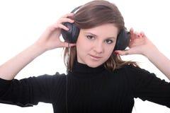Brunette com olhares dos fones de ouvido em linha reta Fotos de Stock Royalty Free