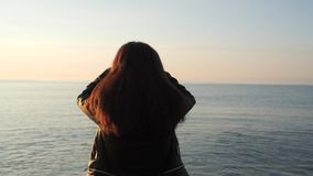Back girl on the pier. Brunette comes to the edge of the pier and looks at the dawn stock video
