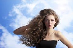 Brunette con el peinado creativo en cielo Fotografía de archivo libre de regalías