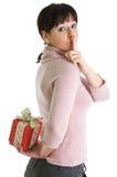 Brunette con el regalo de Navidad ocultado Imagen de archivo