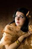 Brunette con la farfalla dell'marrone-oro Fotografia Stock