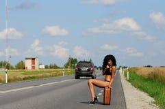 Brunette con la maleta en el camino, carretera. Imagen de archivo libre de regalías