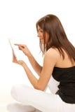 Brunette con la pista de tacto de la tablilla en manos Imagen de archivo libre de regalías