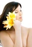 Brunette con las flores amarillas del lirio en balneario Foto de archivo libre de regalías
