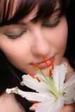 Brunette con las flores del lirio blanco Fotos de archivo