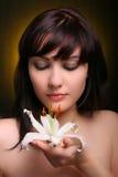 Brunette con las flores del lirio blanco Imagen de archivo libre de regalías