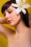 Brunette con las flores del lirio blanco Fotos de archivo libres de regalías