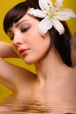 Brunette con las flores del lirio blanco en agua Foto de archivo libre de regalías