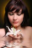 Brunette con las flores del lirio blanco en agua Foto de archivo