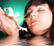 Brunette con las flores del lirio blanco en agua Imagen de archivo libre de regalías