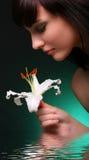 Brunette con las flores del lirio blanco en agua Imagenes de archivo