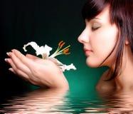 Brunette con las flores del lirio blanco en agua Fotografía de archivo libre de regalías