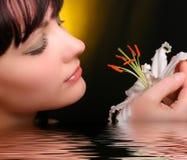 Brunette con las flores del lirio blanco en agua Imagen de archivo