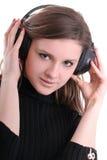 Brunette con miradas de los auriculares derecho Foto de archivo libre de regalías