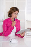 Brunette considering businesswoman in pink jacket at desk. Royalty Free Stock Photos