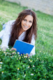 Brunette cool girl with a tablet lying on the grass Stock Photo