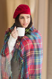 Brunette with cover holding mug and thinking Royalty Free Stock Photo