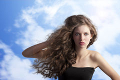 Brunette with creative hairstyle in sky. Beauty fashion portrait of a very young cute brunette with long curly hair with hairstyle flying in the wind on sky Royalty Free Stock Photography