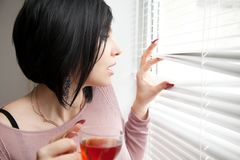 Brunette with a cup peeping through the blinds Royalty Free Stock Photo