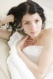 Brunette curl woman lying on bed Royalty Free Stock Photography