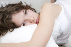 Brunette curl woman lying on the bed Stock Photos