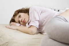 Brunette curl woman lying on the bed Stock Photography