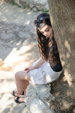 Brunette curly hair lady, sitting under the tree Royalty Free Stock Image