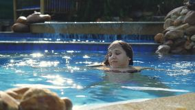 Brunette cute woman enjoys water in swimming pool in slow motion on sunny day while vacation with beautiful sun effects stock video