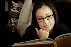 Brunette détendant à la maison avec le livre. Image stock