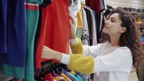 Brunette Dame ist, ansehend berührend und sportive T-Shirts im Kleidungsgeschäft stock video