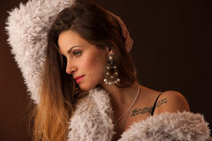 Brunette dancer posing in a white fluffy coat in front of dark background Royalty Free Stock Photos