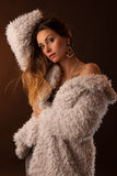 Brunette dancer posing in a white fluffy coat in front of dark background. Long haired brunette dancer posing in a white fluffy coat in front of dark background Stock Images