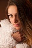 Brunette dancer posing in a white fluffy coat in front of dark background Stock Photos