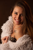 Brunette dancer posing in a white fluffy coat in front of dark background Royalty Free Stock Image