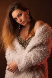 Brunette dancer posing in a white fluffy coat in front of dark background Stock Photography