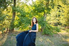 Brunette dancing in a long blue dress Royalty Free Stock Photos