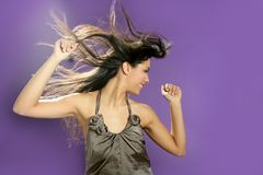 Brunette dancing at studio on purple background royalty free stock photography