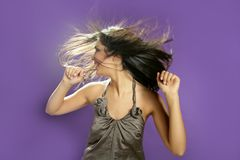 Brunette dancing at studio on purple background Stock Photos