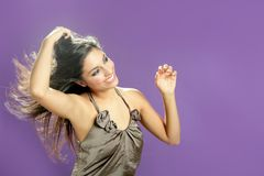 Brunette dancing at studio on purple background Stock Photography
