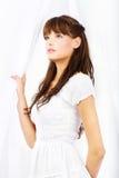 Brunette dans la robe blanche retenant le rideau blanc Photographie stock libre de droits